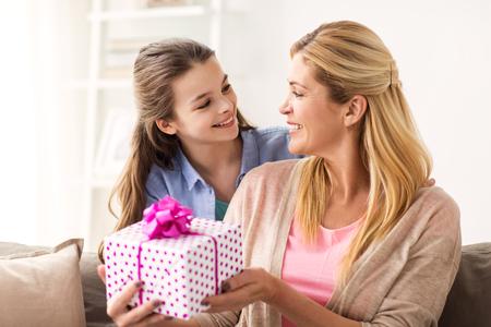 母は自宅に人、休日、家族概念 - の誕生日を与えること幸せな女の子を提示します。