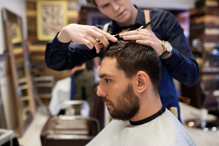 grooming: grooming, hairdressing and people concept - man and barber with comb and scissors cutting hair at barbershop Stock Photo