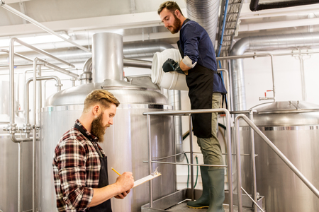 the brewer: manufacture, business and people concept - men working at craft brewery or beer plant
