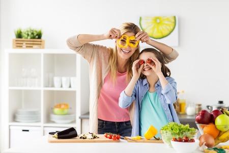 健康な食べること、家族、人々 コンセプト - 幸せな母と娘の夕食の野菜を料理と家庭の台所で楽しい