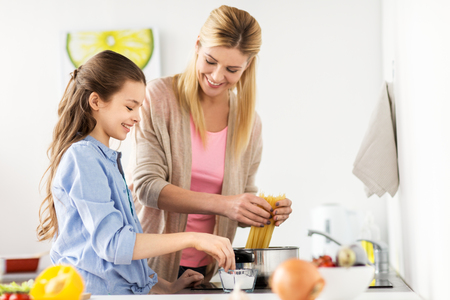 food, family and people concept - happy mother and daughter cooking and boiling spaghetti pasta for dinner at home kitchen Imagens