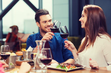 tomando vino: couple dining and drinking wine at restaurant Foto de archivo