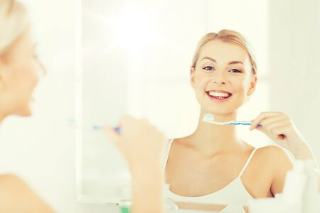 whiten: woman with toothbrush cleaning teeth at bathroom