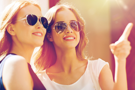 happy women in sunglasses pointing finger outdoors Stock Photo