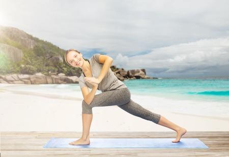 woman doing yoga side angle pose on beach Stock Photo