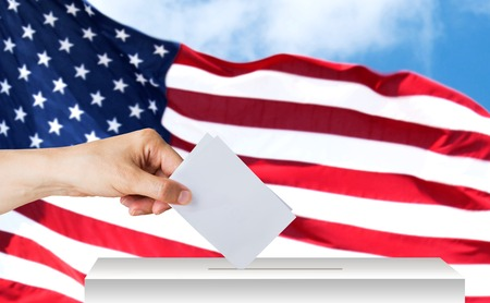 hand of american with ballot and box on election