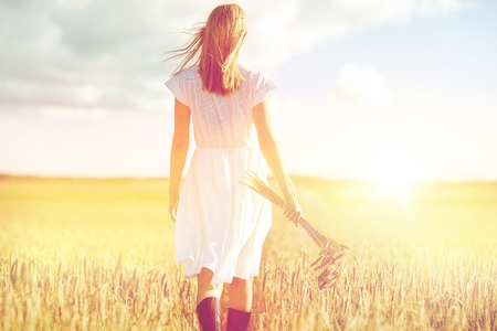 spica: young woman with cereal spikelets walking on field