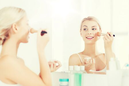 grooming: woman with makeup brush and powder at bathroom Stock Photo