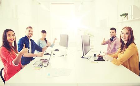 親指を現してコンピューターと創造的なチーム