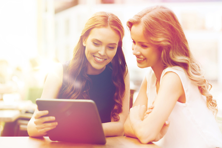 taking video: happy young women or teenage girls with tablet pc