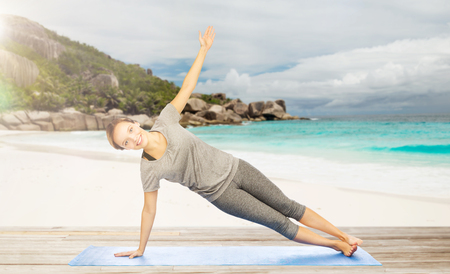 plank position: woman doing yoga in side plank pose on beach