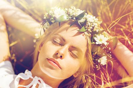 happy woman in wreath of flowers lying on straw