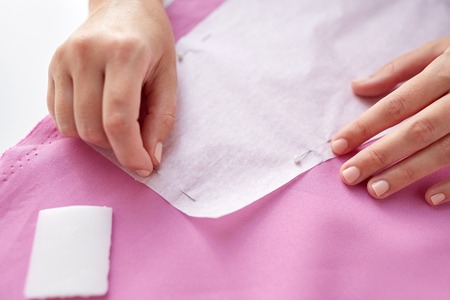 woman with pins stitching paper pattern to fabric Imagens