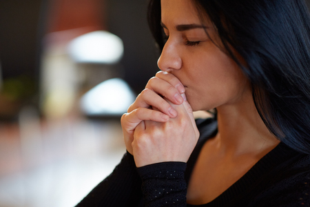 close up of unhappy woman praying god at funeral