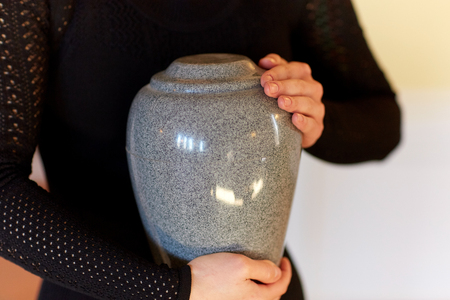 close-up van de vrouw met crematie urn op begrafenis