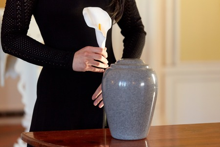 woman with cremation urn at funeral in church Archivio Fotografico