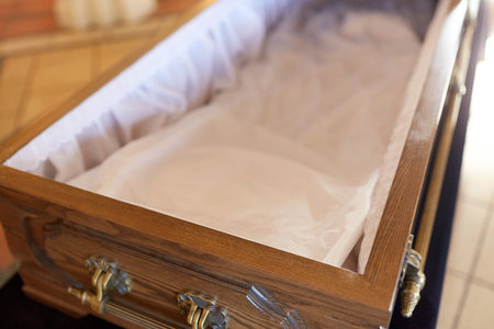 close up of open empty coffin in church