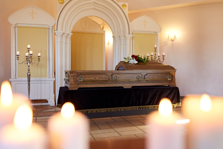 burning candles and coffin in church at funeral