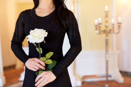 Vrouw met witte roos bij begrafenis in de kerk Stockfoto