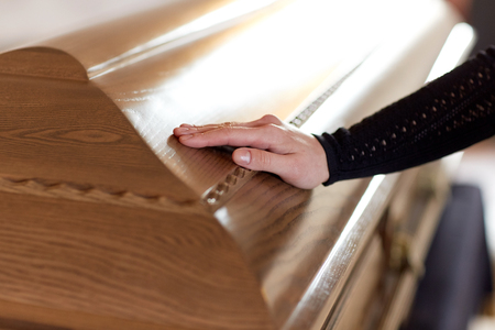woman hand on coffin lid at funeral in church