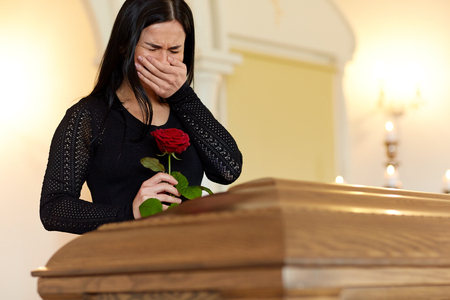 crying woman with red rose and coffin at funeral
