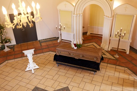 coffin with flowers and stand at funeral in church Stock Photo