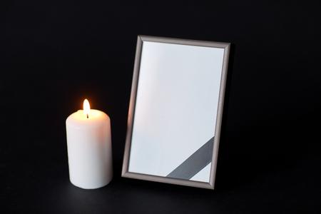 사진 프레임에 검은 리본 및 장례식에 촛불
