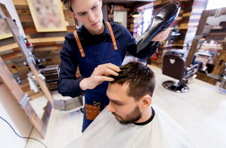 barber with fan drying male hair at barbershop Stock Photo