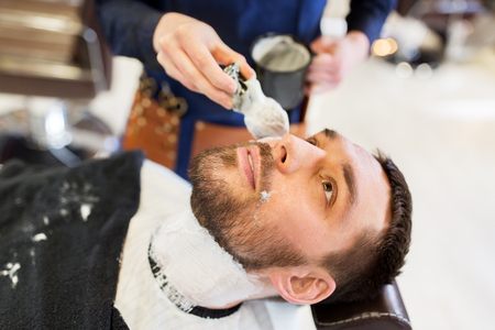 grooming: man and barber applying shaving foam to beard