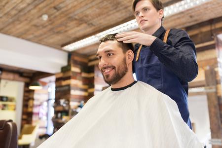 metrosexual: man and barber styling hair at barbershop Stock Photo