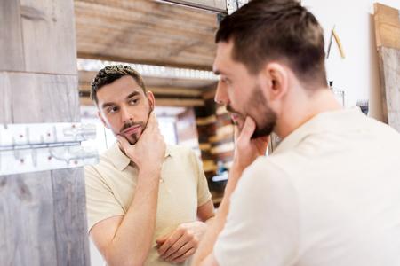 man looking at himself at barbershop mirror