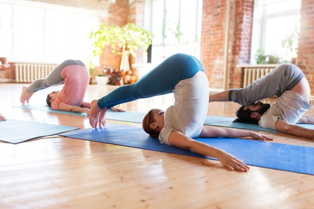 group of people doing plow pose at yoga studio Stock Photo - 80533049
