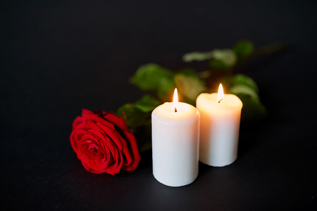 red rose and burning candles over black background Stock Photo - 80533222