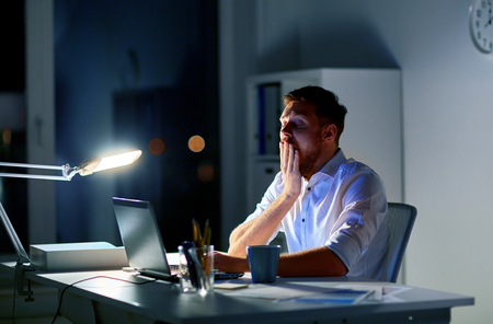 man with laptop and coffee working at night office