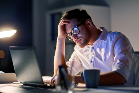 exhausting: businessman with laptop thinking at night office