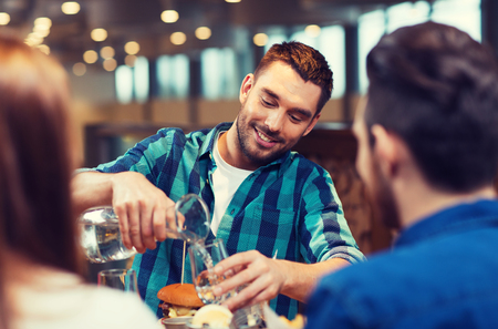 holiday gathering: happy man with friends pouring water at restaurant