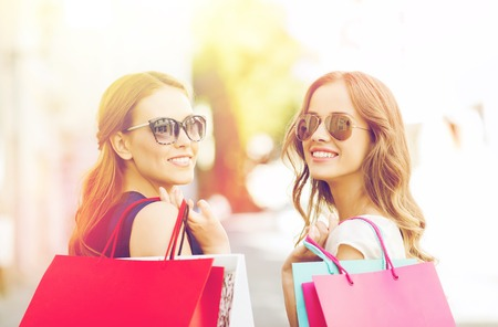 to spend: happy young women with shopping bags in city