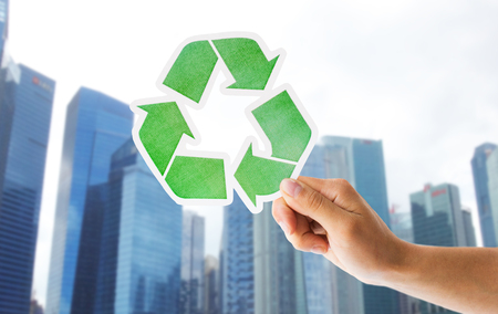 Chiuda in su della mano con ricicla il segno verde in città Archivio Fotografico - 80823010