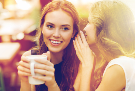 rumour: young women drinking coffee and talking at cafe