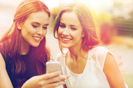 Mujeres jóvenes felices con teléfono inteligente en el café al aire libre Foto de archivo - 80821790