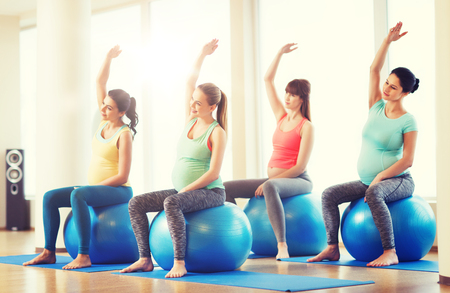 happy pregnant women exercising on fitball in gym Stock Photo - 80711884