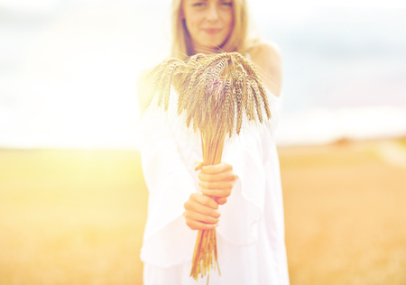 spica: close up of happy woman with cereal spikelets