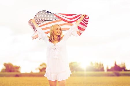 穀物のフィールドの米国旗を持つ幸せな女 写真素材
