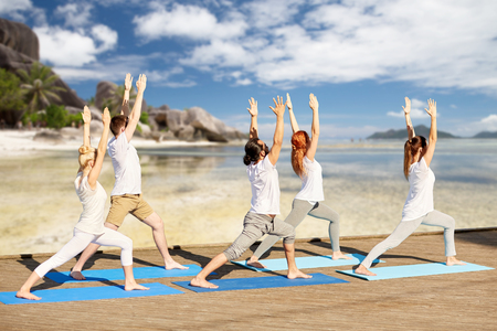 group of people making yoga exercises on beach