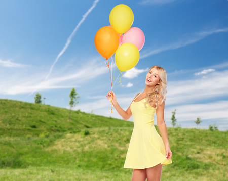 happy woman with helium air balloons in summer Stock Photo