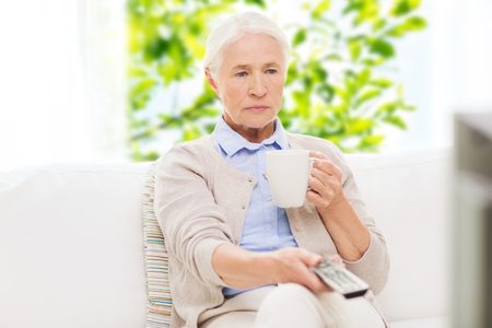 televisor: senior woman watching tv and drinking tea at home