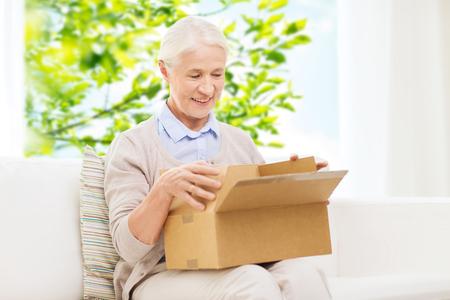 Feliz mujer mayor con caja de paquetes en casa