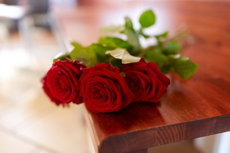 funeral and mourning concept - red roses on bench in church Stock Photo