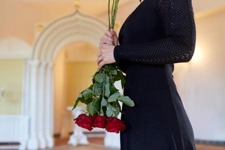 mensen en rouw concept - vrouw met rode rozen bij de begrafenis in de orthodoxe kerk