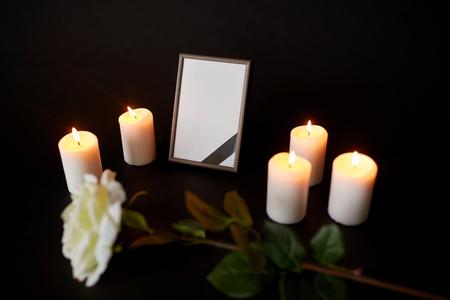 begrafenis en rouw concept - fotolijst met zwart lint, bloem en brandende kaarsen in de duisternis